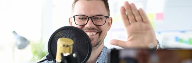 L'uomo sorridente si siede davanti a un microfono e saluta la telecamera con il suo commentatore di sport a mano