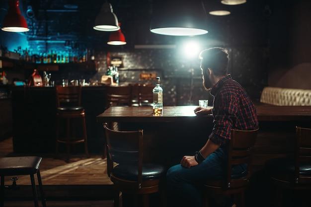 Uomo sorridente seduto al bancone del bar,