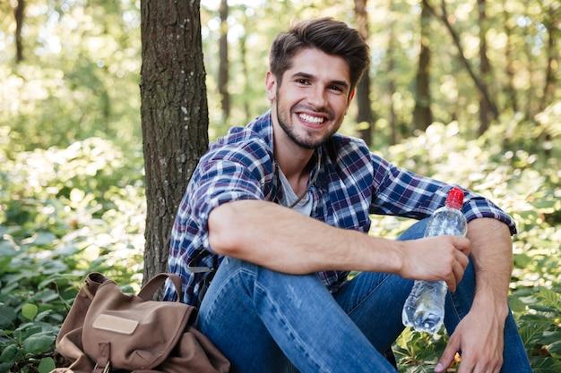 Uomo sorridente seduto nella foresta guardando davanti