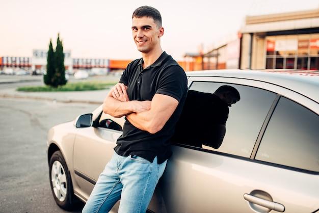 Uomo sorridente in piedi vicino alla sua auto all'aperto, concetto di pubblicità. stile di vita automobilistico. affari automobilistici