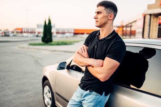 Uomo sorridente in piedi vicino alla sua auto all'aperto