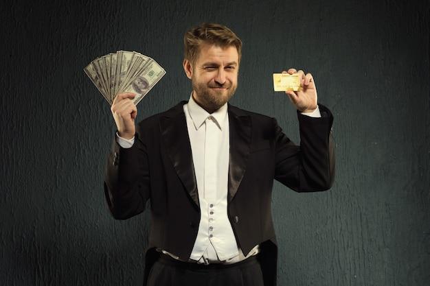 Uomo sorridente in un frac in possesso di una carta di credito e denaro