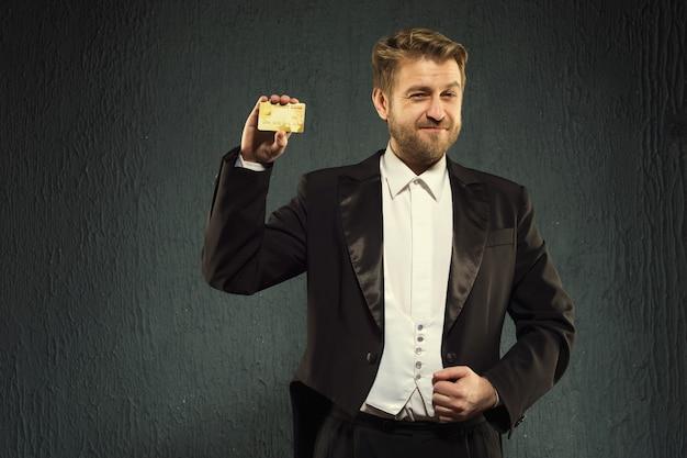 Uomo sorridente in un frac in possesso di una carta di credito