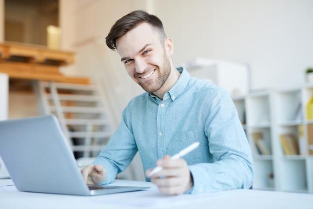 Uomo sorridente che per mezzo del computer portatile