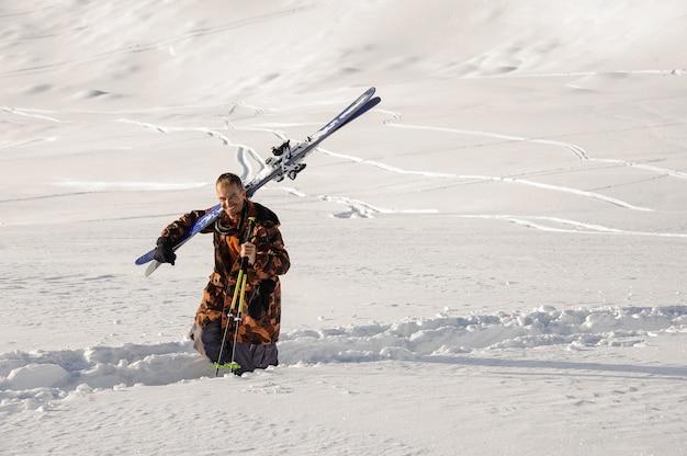 Uomo sorridente camminando sul sentiero calpestato nella neve con gli sci sulla spalla nella famosa località turistica di gudauri in georgia
