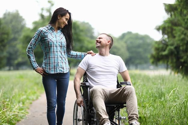 L'uomo sorridente in sedia a rotelle cammina nel parco con la donna