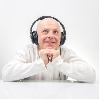 Uomo sorridente in maglione bianco che ascolta la musica sulle cuffie portatili