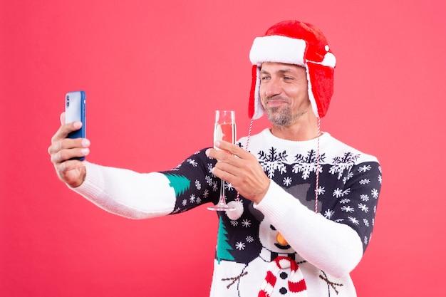 Uomo sorridente in maglione invernale e cappello che fa selfie su smartphone con champagne su sfondo rosso, natale.