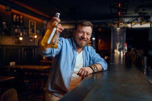 Uomo sorridente con una bottiglia di birra seduto al bancone del bar. una persona di sesso maschile che riposa in un pub, emozioni umane, attività ricreative, vita notturna