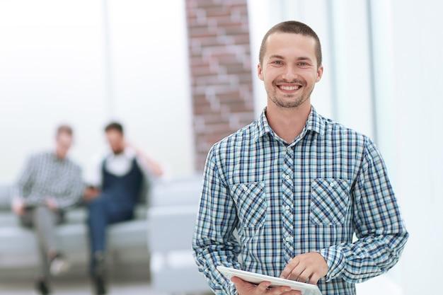 Uomo sorridente con una tavoletta digitale in piedi in ufficio