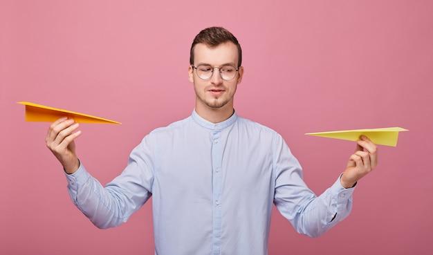 Uomo sorridente con due aeroplani di carta