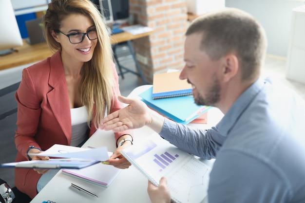 Uomo e donna sorridenti che comunicano e tengono in mano documenti con grafici in mano