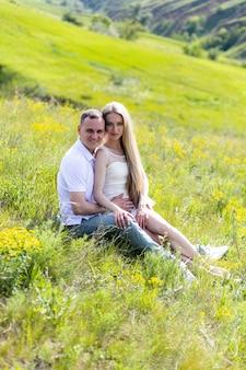 Uomo e donna sorridenti che hanno picnic in campagna. relazioni