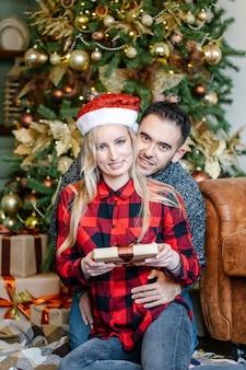 Uomo e donna sorridenti che abbracciano e che tengono il contenitore di regalo, presentandosi i regali di natale l'un l'altro, celebrando le vacanze invernali