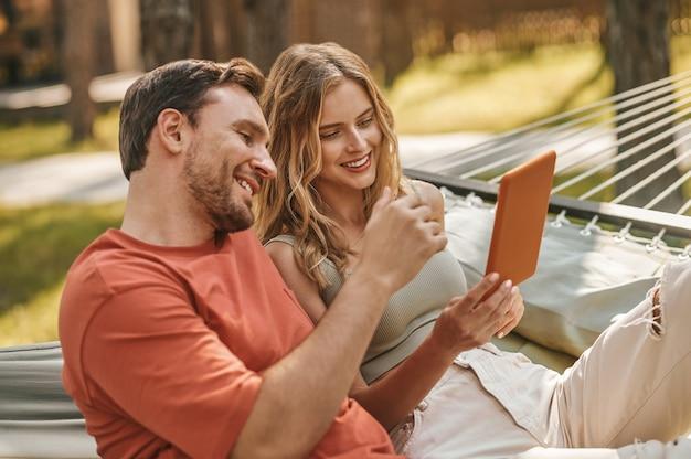Uomo e donna sorridenti che guardano il tablet