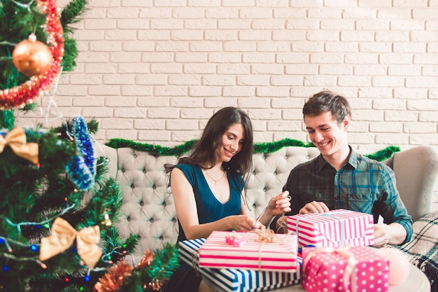 Uomo e donna sorridenti che imballano i regali
