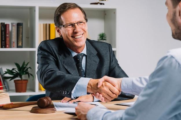 Uomo d'affari maturo sorridente che stringe le mani con il cliente nell'aula di tribunale