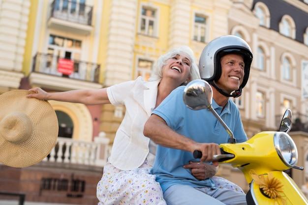 La coppia matura sorridente guida il motorino.