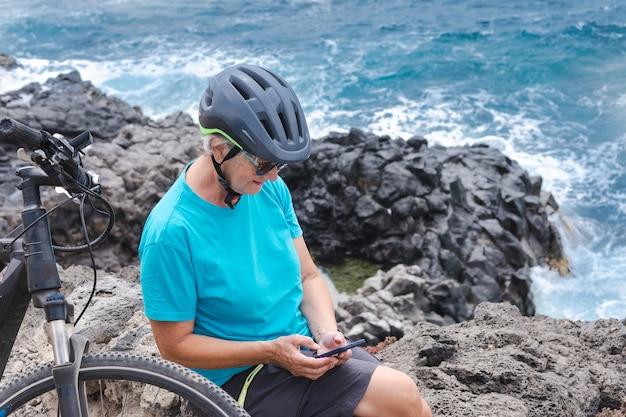 Donna ciclista matura sorridente che si gode una sana attività in mare con bici elettrica utilizzando il telefono cellulare