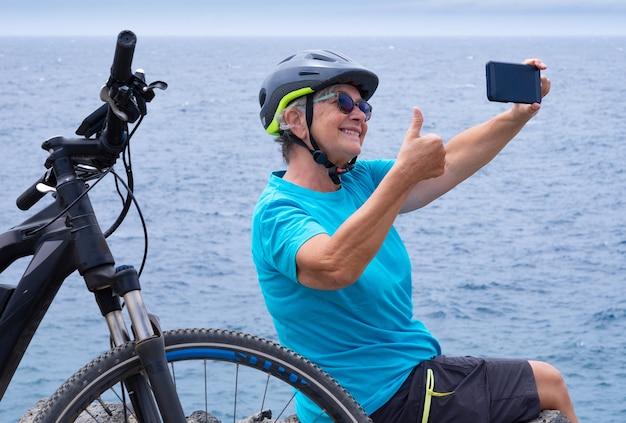 Donna ciclista matura sorridente che si gode una sana attività in mare con la sua bici elettrica