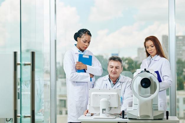 Sorridente medico maturo che mostra i risultati del test medico a giovani stagiste e chiede loro di diagnosticare la malattia