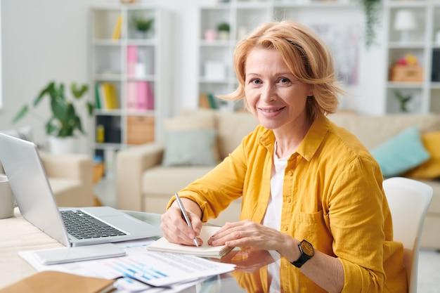 Sorridente femmina matura in abbigliamento casual tenendo la penna su carta mentre si fa un piano di lavoro davanti al computer portatile in soggiorno durante la quarantena