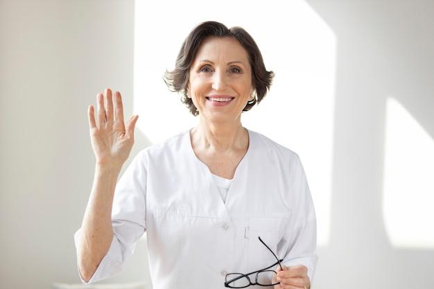 Terapista medico femminile maturo sorridente che guarda l'obbiettivo. operatore medico professionista che tiene una consultazione in videochiamata con un paziente online