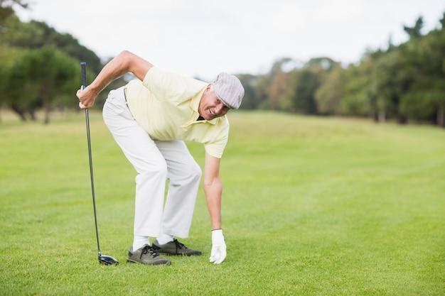 Club di golf maturo sorridente della tenuta dell'uomo mentre piegando sul campo erboso