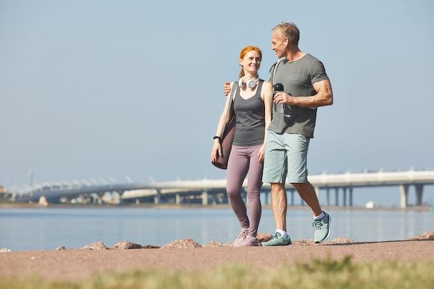 Sorridente uomo maturo con una bottiglia d'acqua che abbraccia la moglie mentre si cammina con lei sulla riva del fiume dopo l'allenamento