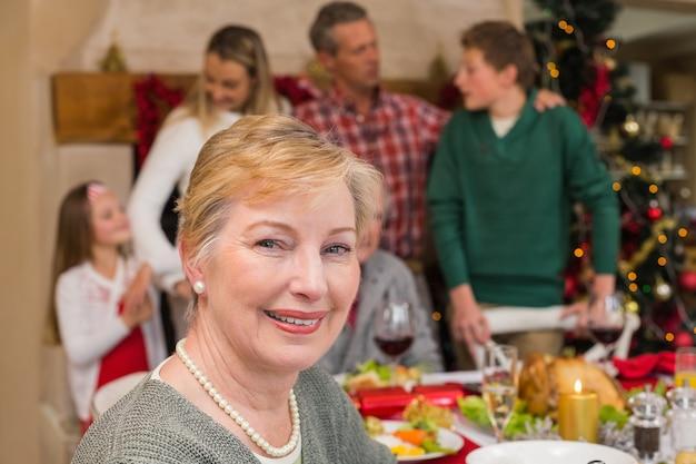 Donna matura sorridente che posa davanti alla sua famiglia