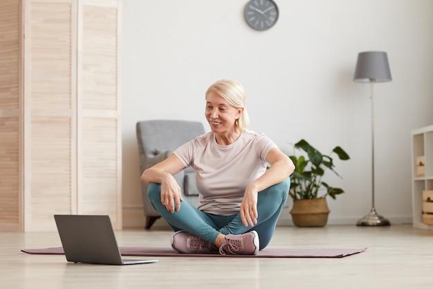 Donna matura sorridente che si siede sul pavimento sulla stuoia di esercitazione e sorridente che guarda formazione sportiva in linea sul computer portatile a casa