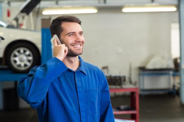 Meccanico sorridente al telefono