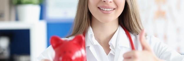 Donna sorridente del medico che tiene in mano un salvadanaio di maiale rosso e fa un gesto con i pollici in su