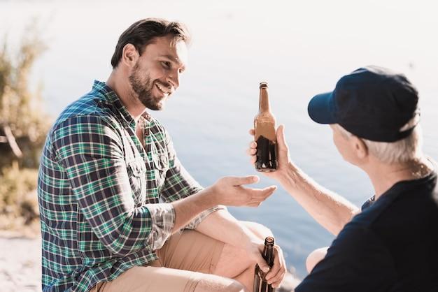 Uomini sorridenti che bevono birra vicino al fiume di estate.