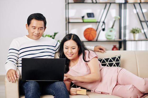 Sorridente coppia asiatica di mezza età in un momento di relax a casa e fare acquisti online tramite laptop