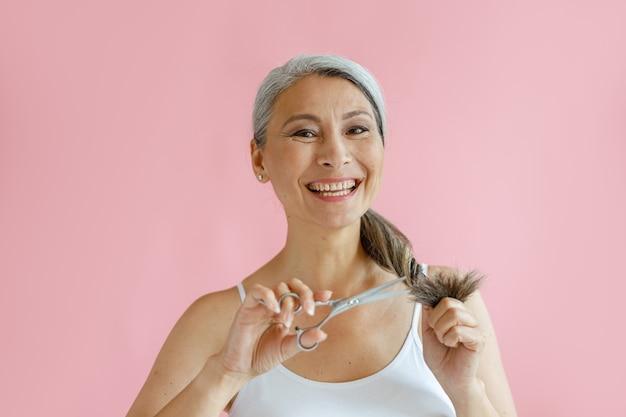 Sorridente signora asiatica di mezza età taglia le estremità sfilacciate di lunghi capelli argentati con le forbici su sfondo rosa in studio. stile di vita di bellezza matura