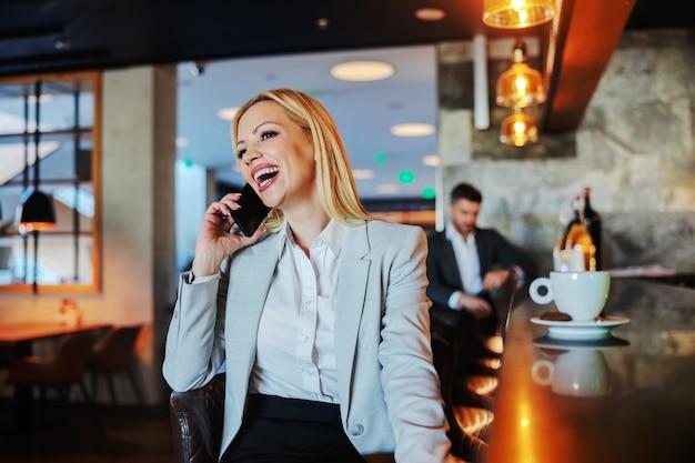 Sorridente bionda di mezza età in abbigliamento formale seduto in un bar di un hotel di lusso e parlando al telefono.
