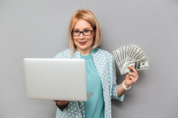 Donna bionda di mezza età sorridente in camicetta ed occhiali che tengono soldi