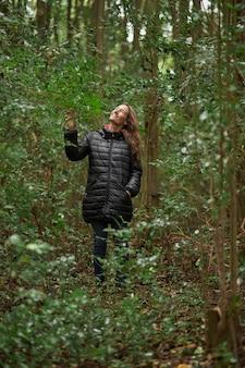 Sorridente donna di mezza età che passeggia nei boschi in inverno, mentre accarezza e si gode il verde. capelli biondi caucasici.