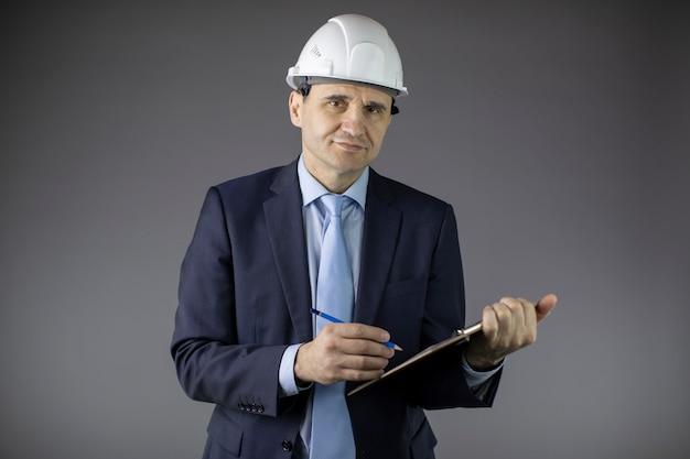 L'ingegnere minerario sorridente in cappello duro prende appunti sulla lavagna per appunti ed esamina la macchina fotografica