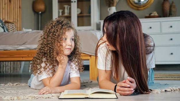 La mamma sorridente legge la favola alla figlia del bambino in età prescolare sul pavimento
