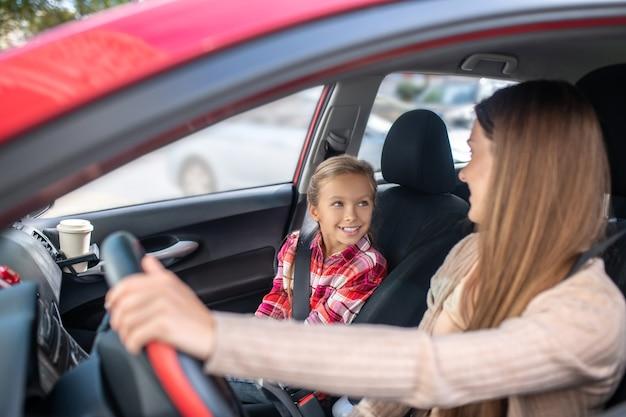 Mamma sorridente seduta al volante, guardando sua figlia