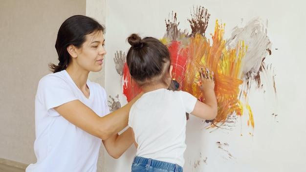 La mamma sorridente in maglietta e guanti neri aggiunge vernici su tela e piccole macchie di figlia con le mani sotto una luce intensa nell'atelier di casa