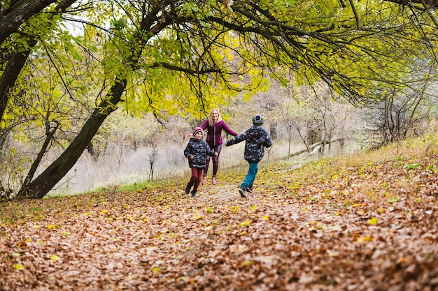Mamma sorridente e gemelli, fratelli corrono su foglie secche cadute sotto gli alberi nella foresta autunnale. week-end attivo in famiglia