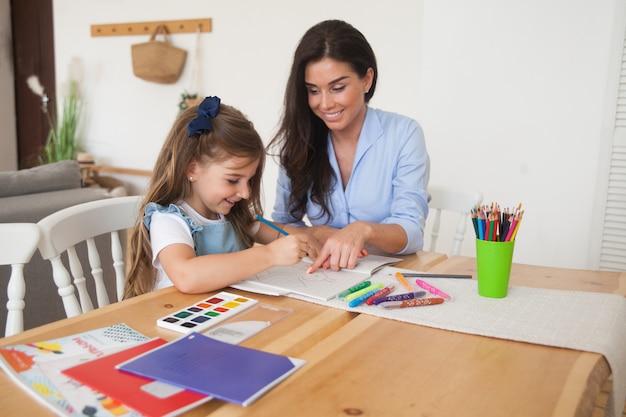 La madre e la figlia sorridenti che preparano per le lezioni e disegna alla tavola con le matite e le pitture