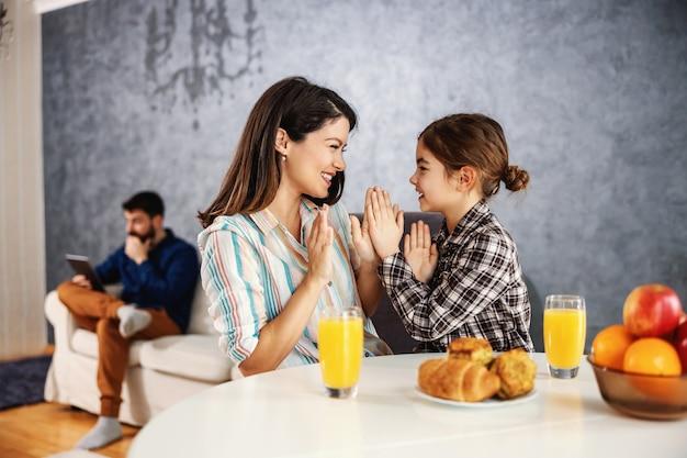 Madre e figlia sorridenti sedute al tavolo da pranzo e giocando a dare una pacca alla torta