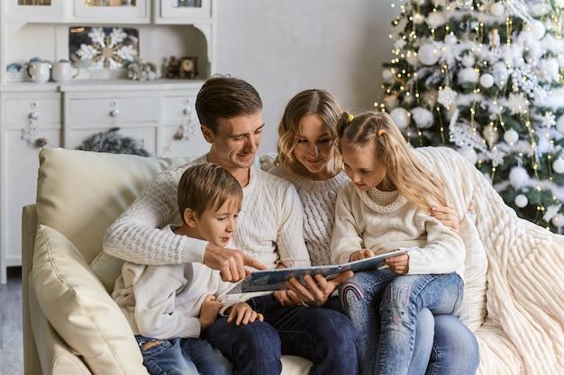 Sorridente madre, padre e bambini che leggono un libro su sfondo di luci