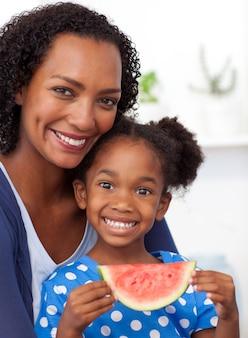 Madre sorridente e sua figlia che mangiano frutta