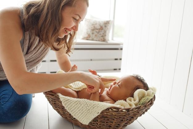 Madre sorridente che gioca con il neonato