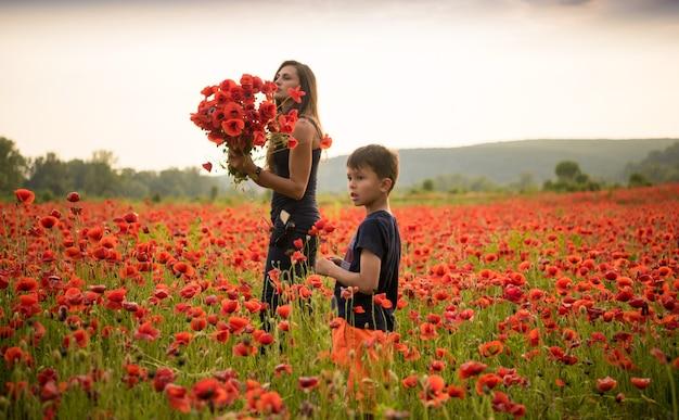 Sorridente madre e figlio in posa sul campo di papaveri al tramonto